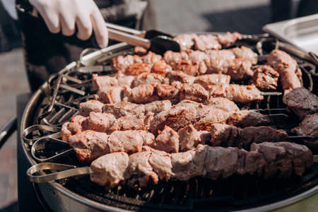 chef prepares meat on a charcoal grill outside at a party
