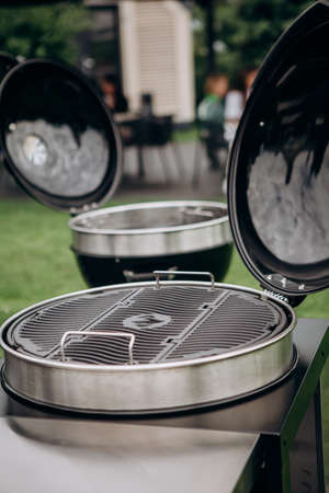 stainless steel charcoal barbecue grill outside on the background of a festive party