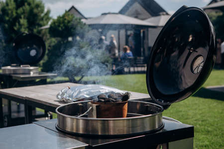 charcoal with smoke in shiny stainless steel barbecue with lid open