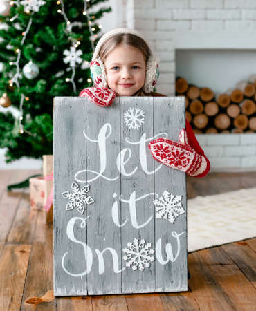 girl in mittens and winter headphones holding a board with the inscription let it snow Stock Photo