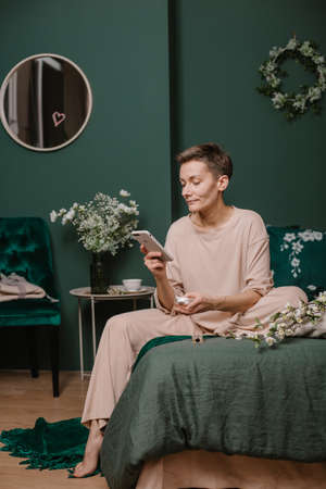 woman with smartphone in stylish bedroom communication chat correspondence mail 版權商用圖片