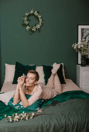 morning woman with perfume bottle and tenderness fashion magazine in stylish bedroom Banque d'images