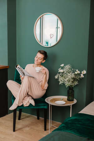 morning women in armchair with cup of tea and fashion magazine bedroom and pajamas
