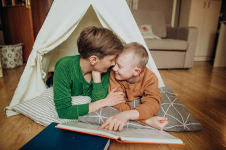 Mom and son lie together in a hut and read a large bright book