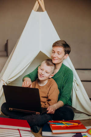 mom and son laptop browsing internet leisure entertainment room child hut 版權商用圖片