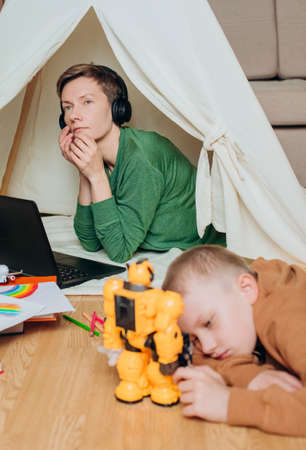 mom works laptop headphones music sound isolation child next plays with a robot