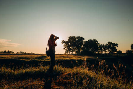 silhouette woman traveler with camera takes pictures of landscape with hills beautiful sunset