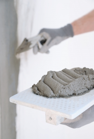 Close-up of construction worker holding a hand cement plaster photo