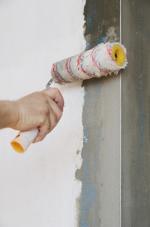 Close-up of construction worker primed the walls of the roller