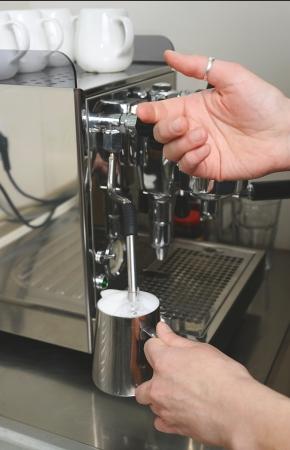 Lait battu par la vapeur sur la machine � caf� Banque d'images