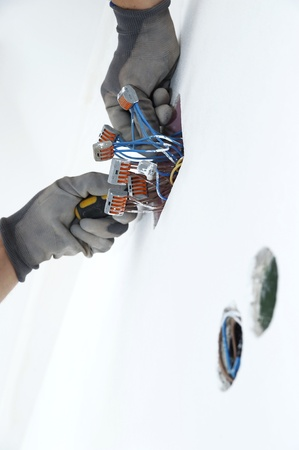 Electrician putting nuts on electrical wires in the box. photo