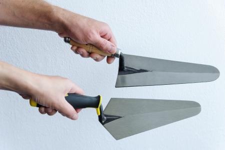 Deux mains avec des truelles sur un fond blanc Banque d'images