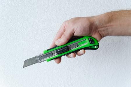 Main de l'homme avec un couteau de coupe sur un fond blanc