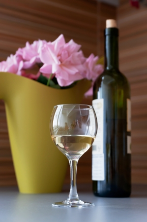 lambrusco: Flowers, a bottle and a glass of white wine on the table