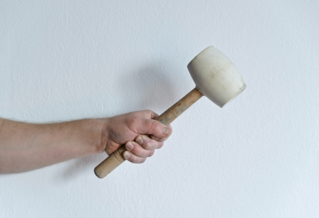 Mans hand holding the rubber mallet background a white wall Stockfoto
