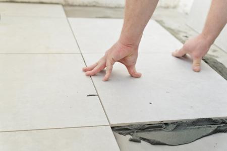 セラミック タイルを置きます。下塗モルタル、コンクリートの床を敷設のための準備で白い床タイルの上に。