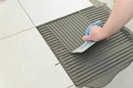 Laying Ceramic Tiles. Troweling mortar onto a concrete floor in preparation for laying white floor tile.