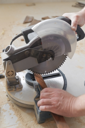 Worker cuts walnut baseboard on the miter saw Фото со стока - 24479317