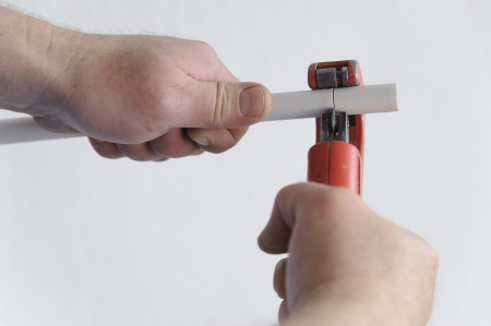 Gros plan sur les mains d'un homme coupant un morceau de tuyau d'eau en PVC