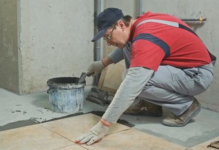 セラミック タイルを置きます。瓦職人の位置に接着剤でセラミック床タイルを置く 写真素材