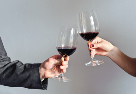 Male and female hands holding glasses with red wine