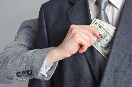 Main f�minine tire de l'argent des hommes de la veste
