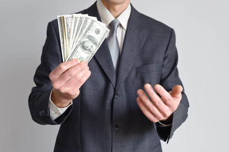 Man in a suit holding money in one hand and the other beckons photo