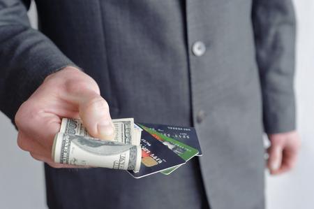 Homme tenant une carte de cr�dit et la facture de cent dollars