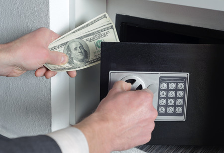 Man with one hand opens the safe  and the other holds money photo
