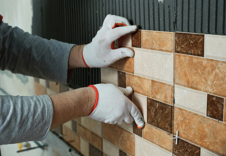 Laying Ceramic Tiles. Tiler placing ceramic wall tile in position over adhesive Фото со стока - 36015070