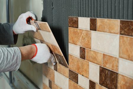 セラミック タイルを置きます。陶磁器の壁のタイルを接着剤で位置に置く瓦職人 写真素材