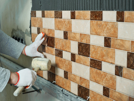tiler: Laying Ceramic Tiles. Tiler knocking on the tiles with a rubber mallet