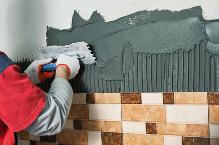 Laying Ceramic Tiles. Tiler deals tile adhesive on the wall
