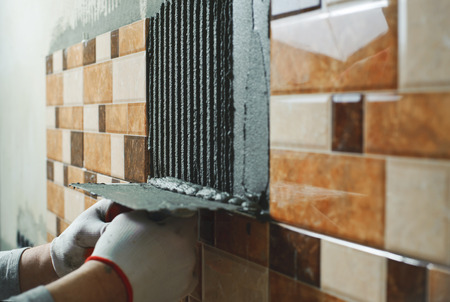 tile adhesive: Laying Ceramic Tiles. Tiler deals tile adhesive on the wall