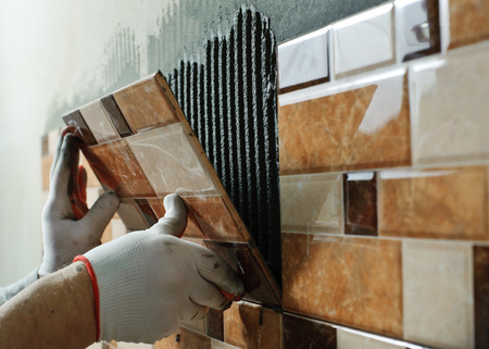 ceramic: Laying Ceramic Tiles. Tiler placing ceramic wall tile in position over adhesive