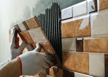 piastrelle bagno: Posa di piastrelle ceramiche. Tiler mettendo mattonelle in ceramica in posizione sopra l'adesivo