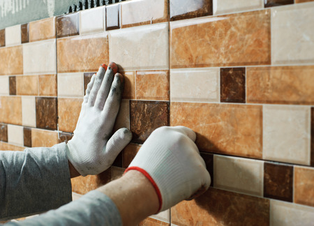Laying Ceramic Tiles. Tiler placing ceramic wall tile in position over adhesive Фото со стока - 36015078