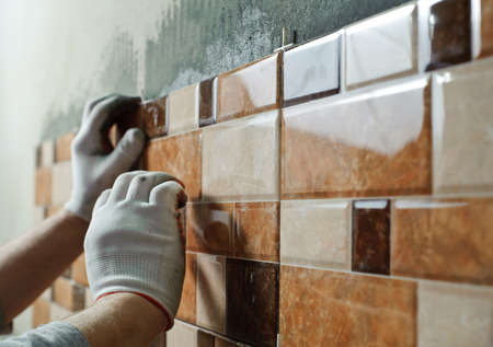 Laying Ceramic Tiles. Tiler placing ceramic wall tile in position over adhesive Фото со стока - 36015079