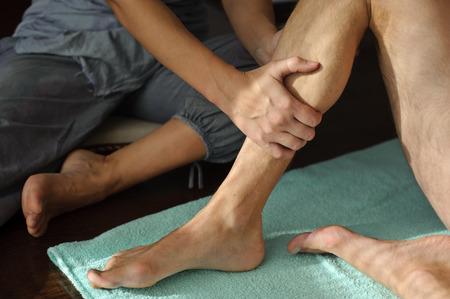 Woman makes a man a foot massage. It massages the lower leg