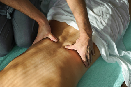 man makes  woman a back massage pressing thumbs