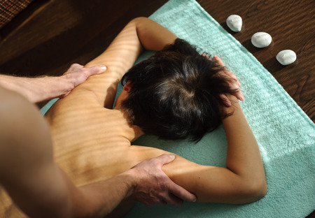 man do back and shoulder massage on a woman Stock Photo