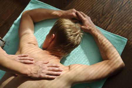A woman makes a man a massage. She massages her back