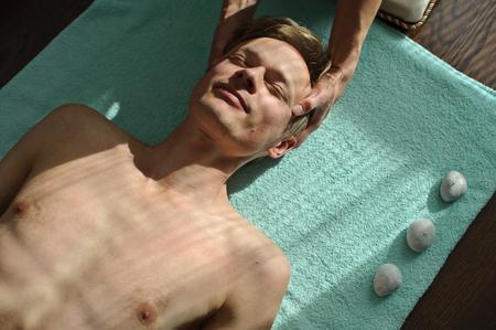 A woman makes a man a massage. It massages the head Stock Photo
