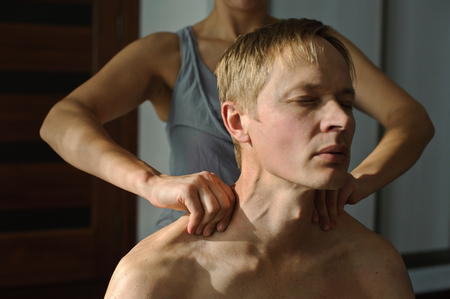 A woman makes a man a massage. She massages her shoulders