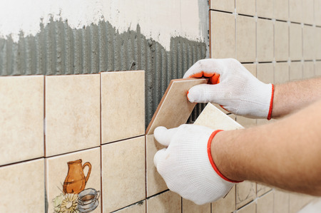 by placing: Worker sets  tiles on the wall in the kitchen. His hands are placing the tile on the adhesive.