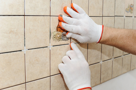 Worker putting tiles on the wall in the kitchen. His hands  inserting the crosses between the tiles to align rows. Stock Photo