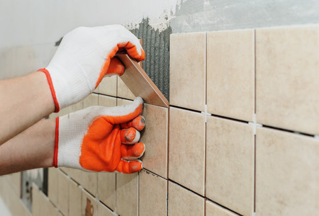 Worker sets  tiles on the wall in the kitchen. His hands are placing the tile on the adhesive. Фото со стока - 63081415
