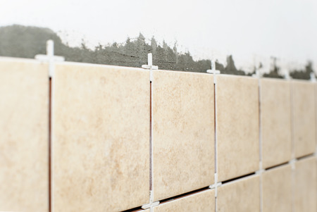 Ceramic tiles with plastic crosses on the kitchen wall.