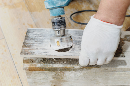 Tiler carves a hole in the tile using a diamond crown. Stock Photo