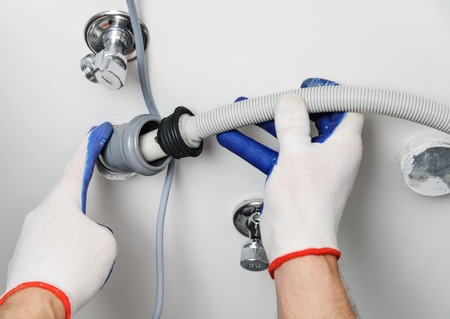 Installation of household appliances. Workman attaches a drain hose to a sewage pipe. Фото со стока